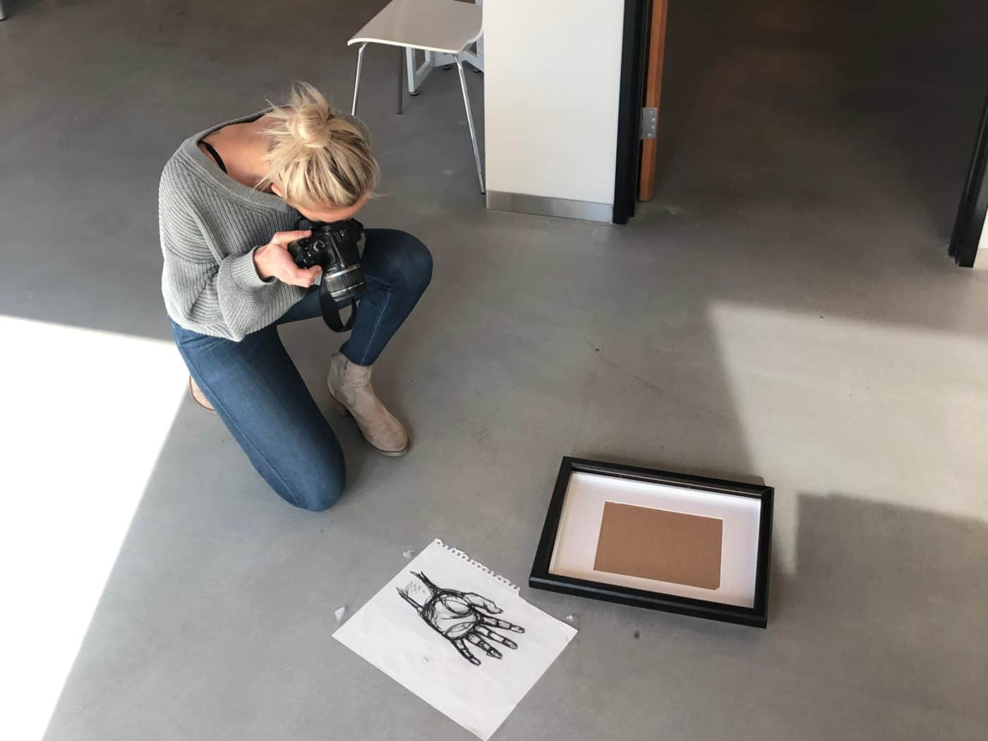 a woman taking a photograph of a drawing of a hand