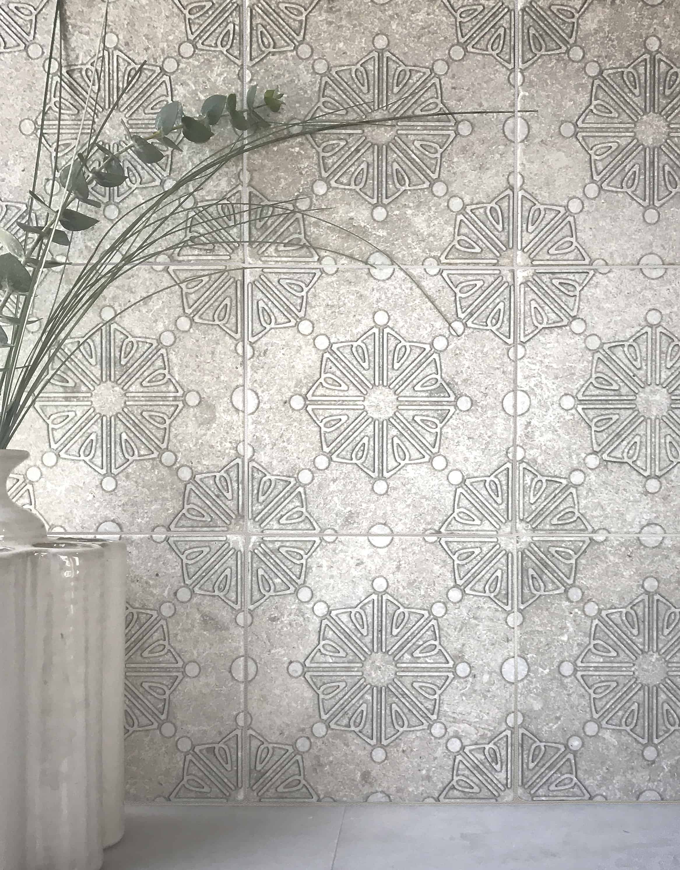 Dahlia pattern Tile in the Pearl color on Perle Blanc limestone as a wall with a fern