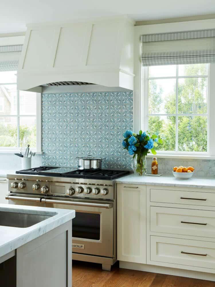 Petals pattern in blue on honed carrara kitchen backsplash